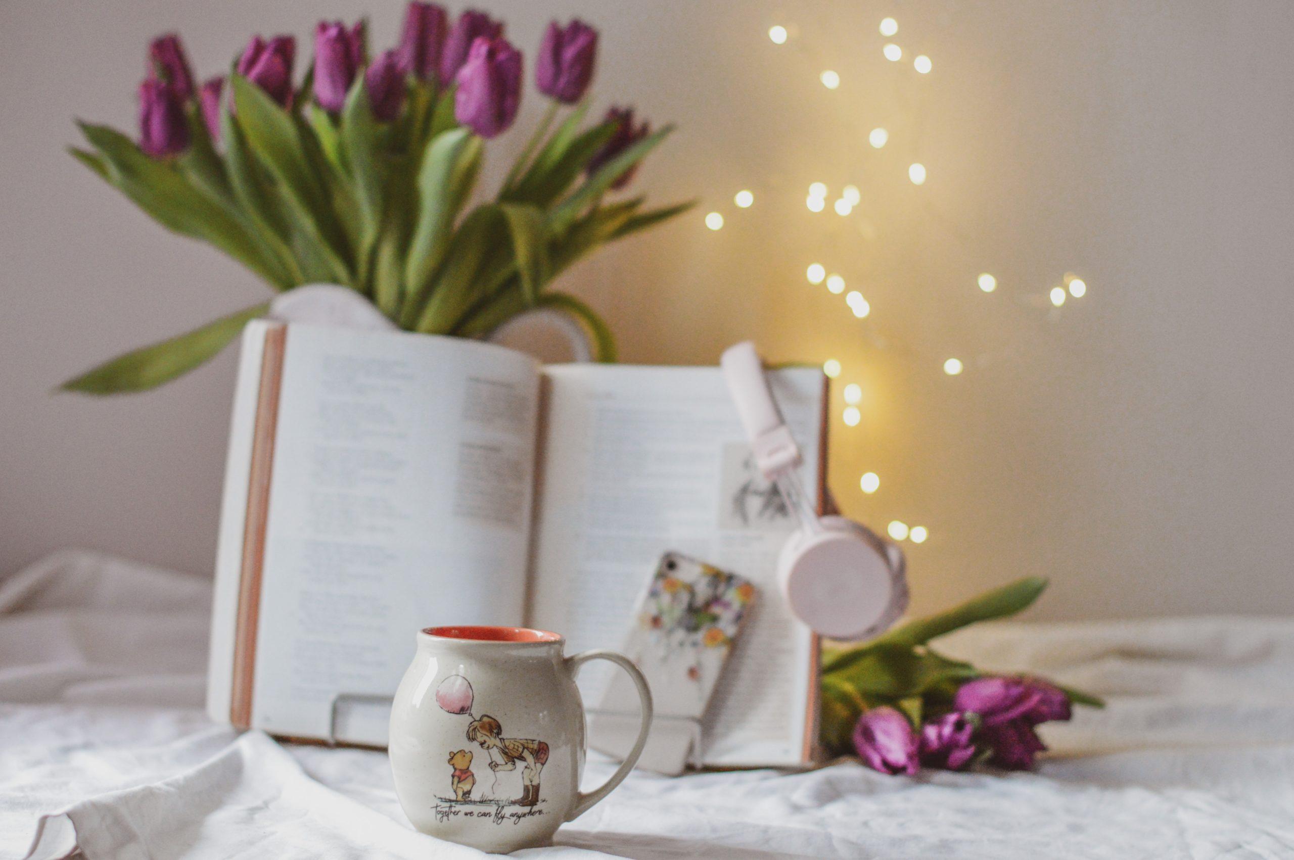 iphone, bukiet tulipanów, kubuś puchatek, kubek, książka, bladoróżowe słuchawki